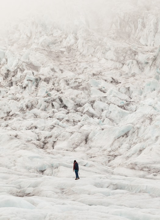 A person at the bottom of a massive ice fall on Falljökull outlet glacier