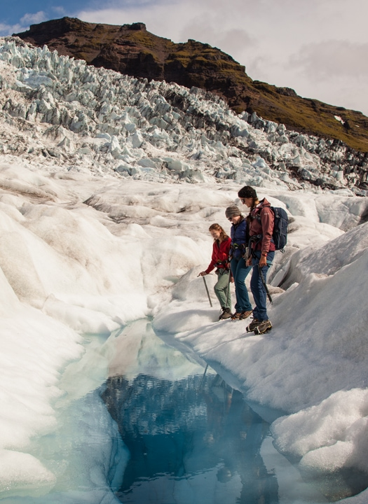A group on a glacier hike standing next to a blue pool on a glacier in Iceland