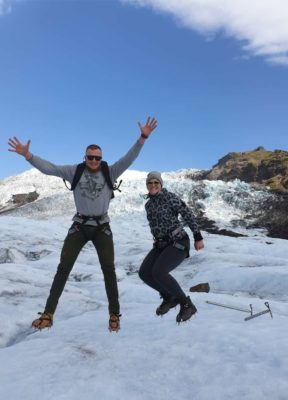 Two happy people jumping for a photograph on the glacier
