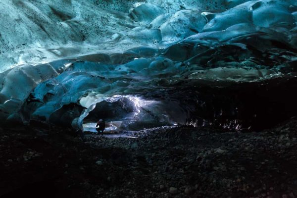 A person photographs blue ice cave that is only reachable by helicopter