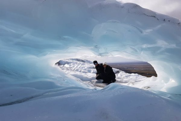 looking-at-a-couple-through-a-beautiful-blue-hole-on-a-glacier-hike-on-falljokull-outlet-glacier-in-iceland