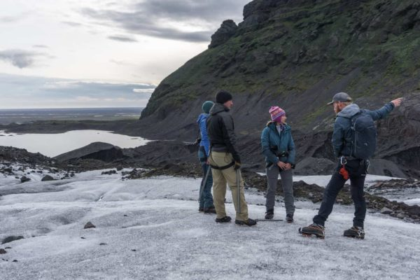 A guide explains the various features of the glacier during an evening glacier walk