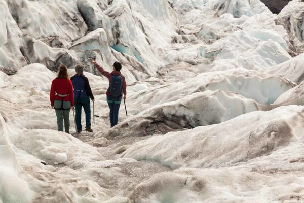 A certified glacier guide leads her group through the rugged ice terrain on a glacier hike on an outlet glacier in Iceland