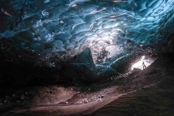 A certified glacier guide stands at the entrance to a large blue ice cave that is only reachable by helicopter