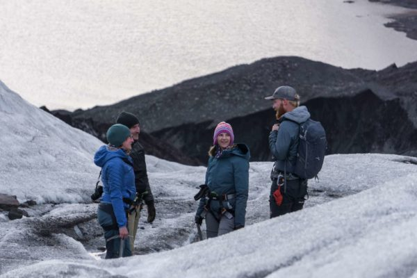 A certified glacier guide explaining the various features of the glacier, to his group during an evning glacier hike.