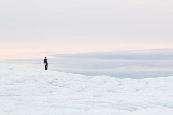 A guide standing and overlooking the glacier and vast plains during an exclusive blue ice cave tour