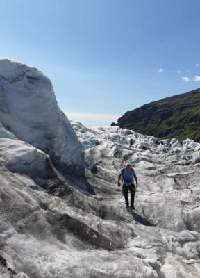 A man walks beneath massive ice sculptures on a glacier tour in iceland