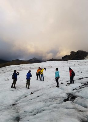 A man takes a photo of a couple as the rest of their group watches, they are standing on a glacier during their evening glacier tour.