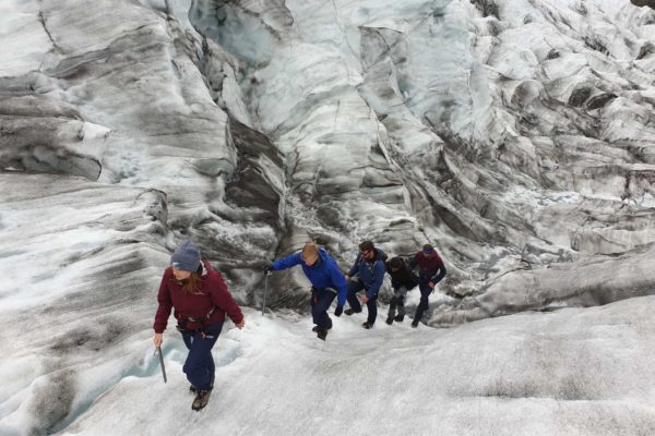 A group walks up the steep glacier terrain on a glacier hike