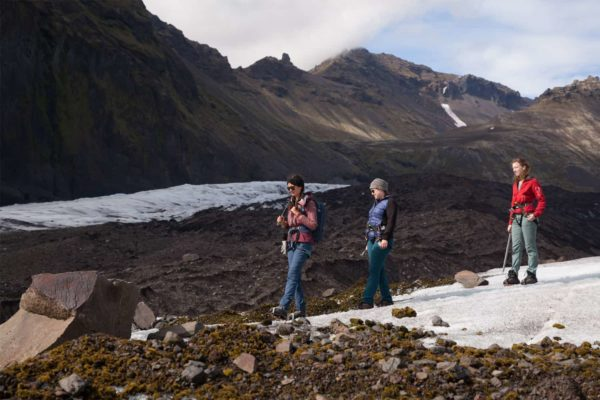A group descends from their glacier tour, walking past rocks and moss laying on the ice.