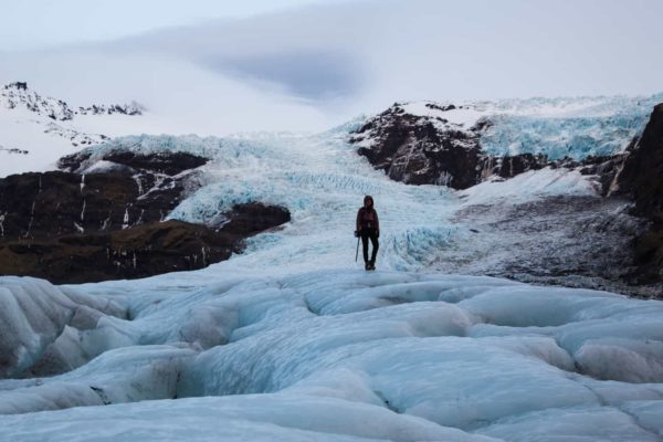 A person walks down the glacier after having visited the blue ice cave