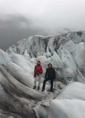Two people standing in between large crevasses on a misty day on the glacier