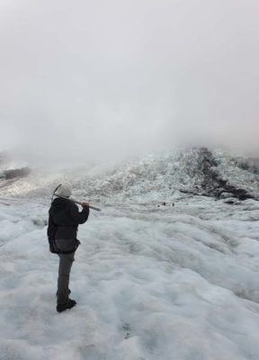 Woman looks at the partially fog covered glacier during her glacier hike