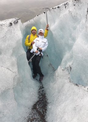A couple poses next to ice walls on a rainy day during their glacier hike on Falljökull outlet glacier in Iceland.