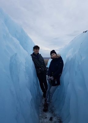 A couple poses in a very blue crevasse on a 3 hour glacier hike in Iceland.