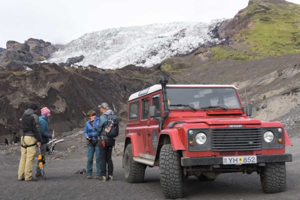 A group getting ready to head up Falljökull outlet glacier. They're standing next to a red Land Rover Defender at the bottom of the glacier.