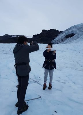 Boy photographs a girl eating a big chunk of ice during their glacier hike on Falljökull, Iceland.