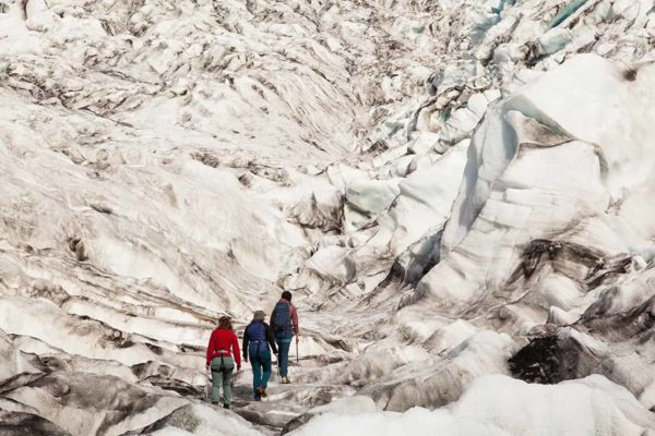 A guide leads her group through the rugged glacier terrain on the glacier hike tour.