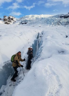 A couple poses in a little, snow filled crevasse during a glacier hike in the winter time.