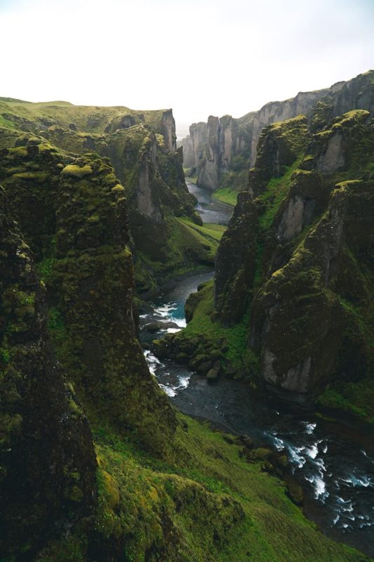 Fjaðrárgljúfur in Iceland. Massive canyon that has a small river inside of it. The canyon is covered with green grass.