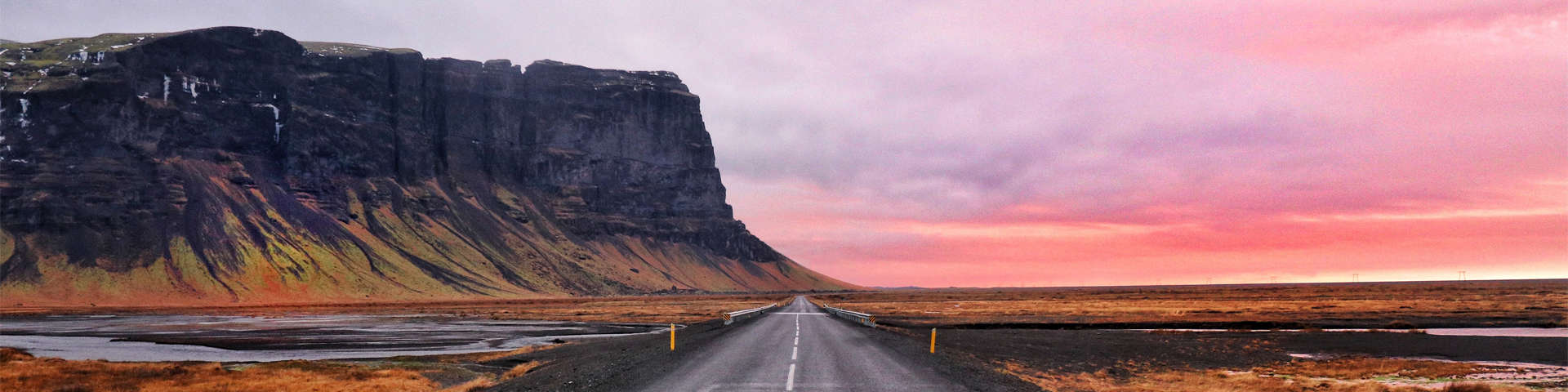 Lómagnúpur, a large mountain overlooking the road ahead during sunset.