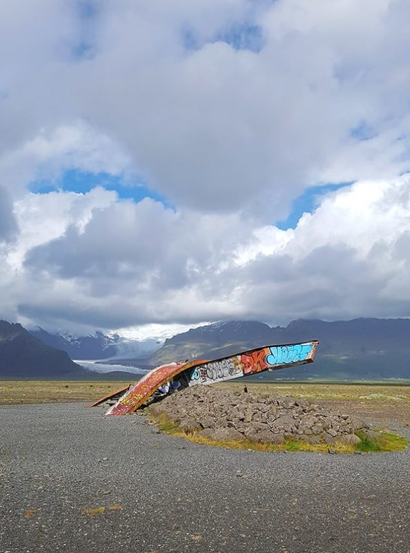 Two steel girders on Skeiðarásandur that have been painted with graffiti. They are standing in a black sand plain with a glacier in the background. they are remains of a bridge that was damaged in jökulhlaups.