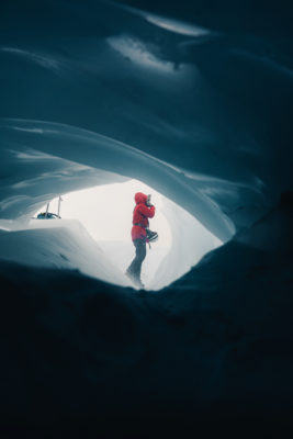 a girl standing outside an blue ice cave