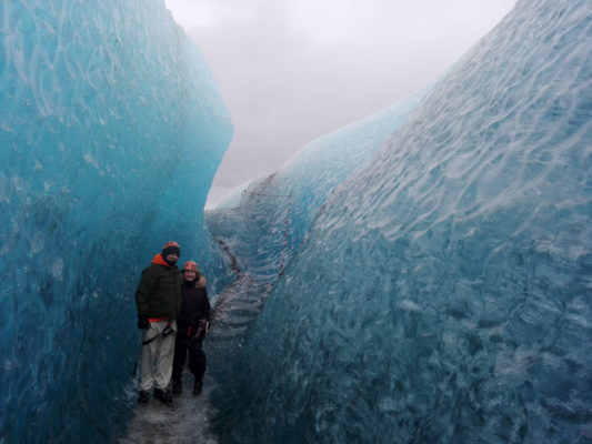 a pair on a glacier hike standing at the bottom of a crevasse with steps behind them.