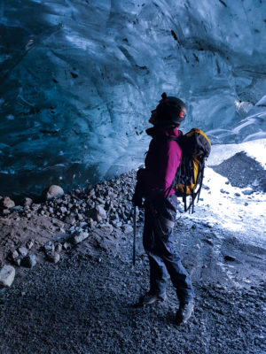 a girl wearing glacier equipment, crampons, harness, helmet, ice axe and a backpack stands beneath a blue ice wall in an ice cave