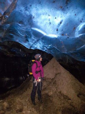 a girl wearing glacier equipment, crampons, harness, helmet, ice axe and a backpack standing next to a pile of volcanic ash inside a blue ice cave