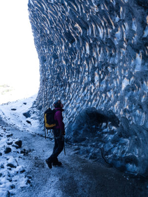 a girl wearing glacier equipment, crampons, harness, helmet, ice axe and a backpack stands beneath a blue ice wall in front of an ice cave