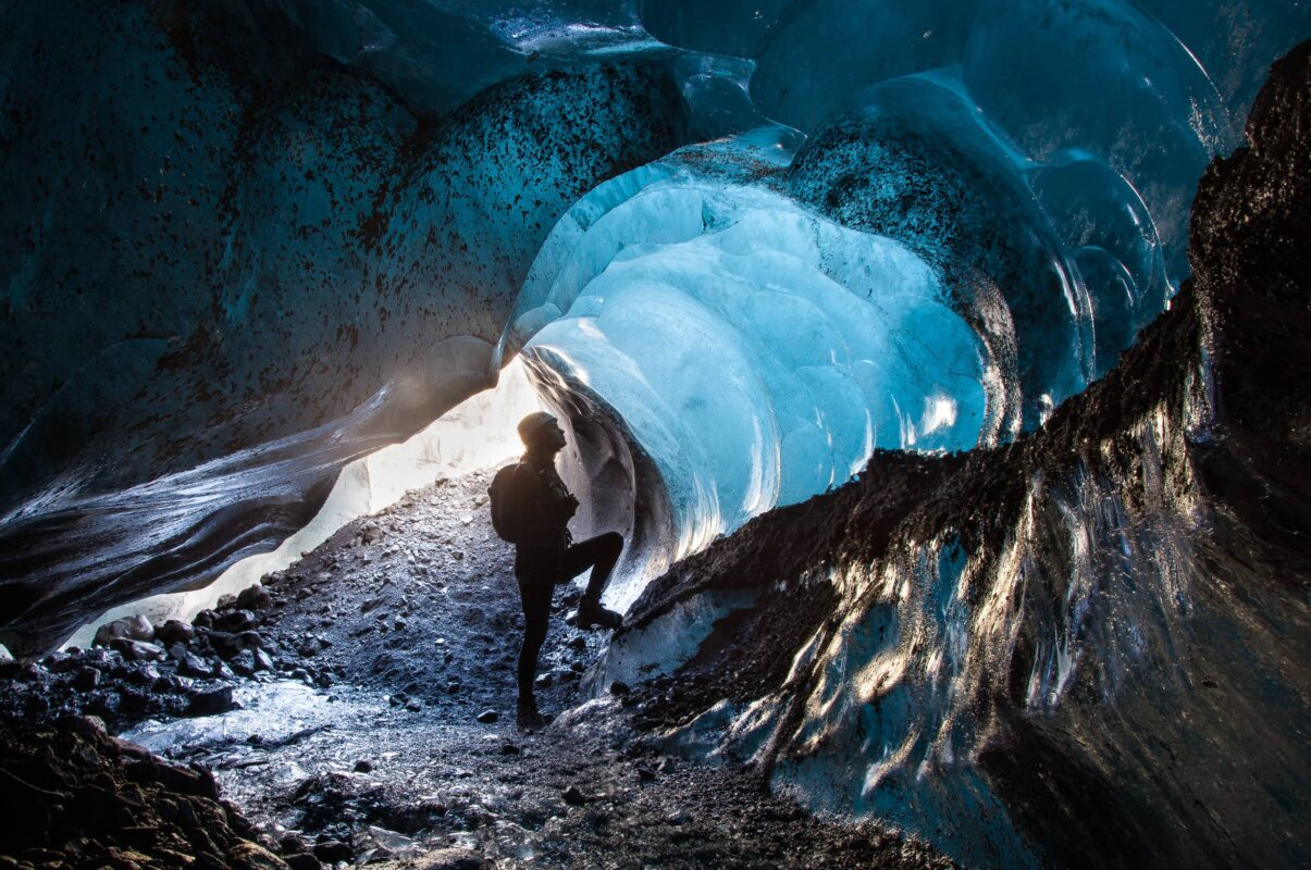 A glacier guide standing in the middle of a small blue ice cave in Skaftafell, Iceland.